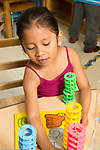 Education Preschool 4-5 year olds girl playing with puzzle and colorful stacking manipulative toys talking and playing by herself