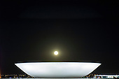 Brasilia, DF, Brazil. National Congress buildings by architect Oscar Niemeyer; the dish at night with the full moon low over it. Praca dos Tres Poderes.