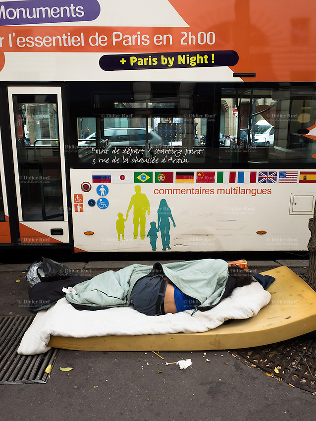 France. Ile-de-France. Paris. A homeless man sleeps on a foam mattress in the street. A tourist bus advertises a two hours tour of Paris by day and night with multilingual comments. 29.09.16 © 2016 Didier Ruef