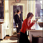 Woman standing at counter in cafe with man coming through door in background