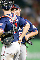 Minnesota Twins first baseman Michael Cuddyer #5 smiles and laughs with teammate Joe Mauer #7 during a pitching change at the Major League Baseball game against the Texas Rangers at the Rangers Ballpark in Arlington, Texas on July 27, 2011. Minnesota defeated Texas 7-2.  (Andrew Woolley/Four Seam Images)