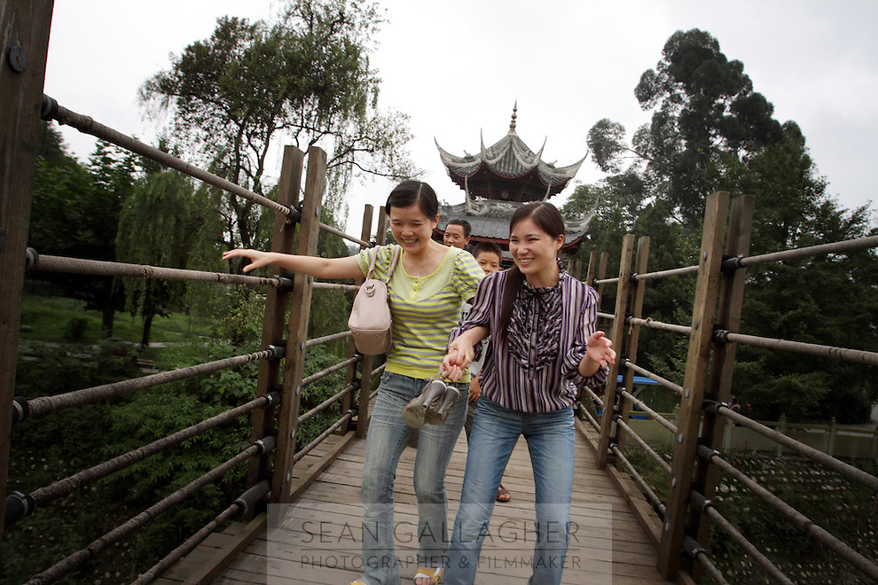 """Tourists visiting the Dujiangyan Irrigation System. The system is regarded as an """"ancient Chinese engineering marvel."""" By naturally channeling water from the Min River during times of flood, the irrigation system served to protect the local area from flooding and provide water to the Chengdu basin. Sichuan Province. 2010"""