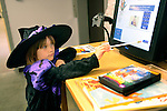 Vivi Mellow, 6, checks out some books and DVDs at the Carson City Library Monday, Oct. 27, 2014 after a completing a craft project. As part of the library's Halloween festivities, dozens of children decorated pumpkins or gourds and took part in a costume contest.