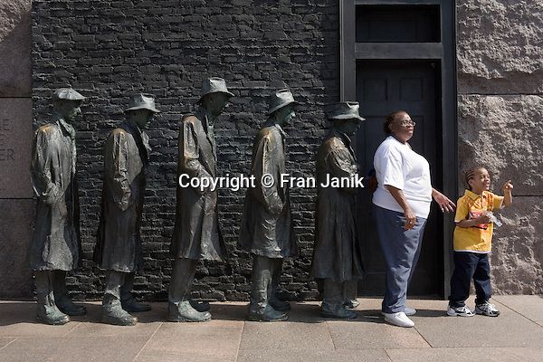 A woman and a young boy pose in front of a sculpture at the FDR Memorial in Washington DC. The sculpture depicts a bread line during the great depression in the United States.