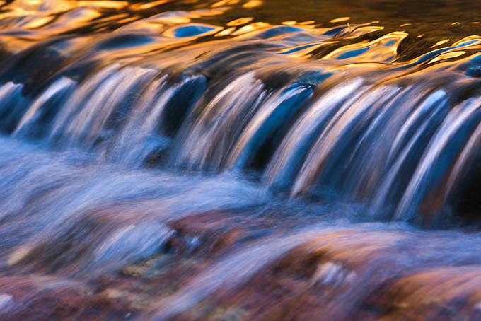 A cascade of water deep in the backcountry of Zion National Park reflects gold and blue colors from the cliffs and sky above.
