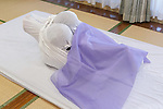 A woman is wrapped in cloth during an Otonamaki (adult wrapping) therapy session on February 4, 2017, Tokyo, Japan. Otonamaki is a Japanese therapeutic method to reduce stiffness and posture problems. A participant, monitored by a health care professional is wrapped in a large piece of breathable cloth, like a sheet, to alleviate posture problems and body stiffness for about 15 to 20 minutes. The therapy comes from Ohinamaki, the practice of wrapping up babies in cloth in a similar way to give them a feeling of security and help them with their physical development. (Photo by Rodrigo Reyes Marin/AFLO)