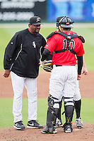 Kannapolis Intimidators pitching coach Jose Bautista (38) chats with his pitcher and catcher on the mound during the South Atlantic League game against the Greenville Drive at CMC-Northeast Stadium on April 6, 2014 in Kannapolis, North Carolina.  The Intimidators defeated the Drive 8-5.  (Brian Westerholt/Four Seam Images)