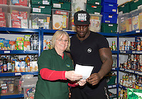 Adebayo Akinfenwa of Wycombe Wanderers - How the strongest man in football is spreading the Christmas cheer. <br /> <br /> Interview and feature will be shown on Sky Sports News HQ and across Sky Sports digital platforms Christmas Day.<br /> <br /> Bayo Akinfenwa helps out Chief operating manager Carol Bestride (left) at a Food Bank in Lewisham, England on 23 December 2016. <br /> <br /> Photo by Alan  Stanford / PRiME Media Images.