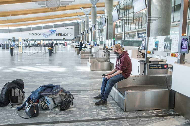 A man with mask (PPE) checking his phone. <br />  <br /> Norwegian authorites introduced measures to combat the Coronavirus (COVID-19)  leaving Gardermoen Airport, near the Norwegian capital Oslo, deserted. <br /> <br /> Restriction on public gatherings and travel have grounded most airplanes, and stopped nearly all domestic and foreign travel. <br /> <br />  Like most capitals, Oslo is usually busy on a Saturday night. But on the first weekend after Norwegian authorites introduced measures to combat the Coronavirus (COVID-19) the city was almost deserted. <br /> <br /> Restriction on public gatherings, closure of schhols, new rules for those serving food and drinks, and fear of further spread of the virus compelled most bars and restaurants to close. <br /> <br /> 28,5 million passangers used the airport in 2018, with the airline Norwegian flying the most people. At teh time of writing Norweigan is on the verge of bankruptcy, and hoping to get governemnt aid to surive the economic crisis caused by the corona virus.  <br /> <br /> <br /> ©Fredrik Naumann/Felix Features