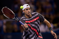 John Isner hits a volley at the net during the Legg Mason Tennis Classic at the William H.G. FitzGerald Tennis Center in Washington, DC.  Unseeded Xavier Malisse defeated American John Isner in three sets in a thunderstorm delayed evening session.