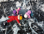 Three children looking into ice on Great Slave Lake.
