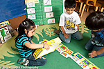 Education preschool 3-4 year olds two boys and agirl pubbing together floor puzzle using picture on box to plan, working together