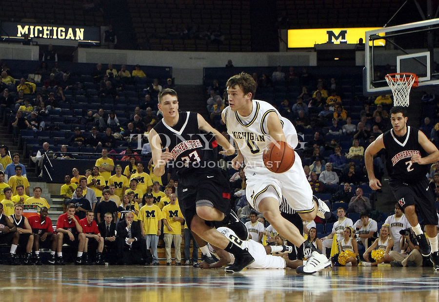Northeastern guard Matt Janning (23) defends Michigan guard Zack Novak (0) in the second half of the regional round championship game of the 2K Sports Classic college basketball tournament, Wednesday, Nov. 12, 2008, in Ann Arbor, Mich. Michigan won 76-56. (AP Photo/Tony Ding)