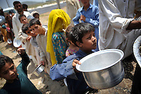 Children wait in line for food at the Swabi refugee camp. Three times a day hot meals are distributed in the camp. At present there's a lack of cooking facilities where the people can cook themselves. The Swabi camp is run by Red Cross/Red Crescent (ICRC) and and is home to about 18,000 refugees. The Pakistani government began an offensive against the Taliban in the Swat Valley in April 2009, which led to a major humanitarian crisis. Up to two million civilians were estimated to have been displaced by the fighting.