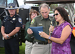 Nevada Highway Patrol Chief Troy Abney and Carson City Sheriff's DARE Officer Lisa Davis watch as Sen. Harry Reid's representative Yolanda Garcia reads a proclamation to Sheriff Ken Furlong during the 11th annual National Night Out hosted by the Carson City Sheriff's Office in Carson City, Nev., on Tuesday, Aug. 6, 2013. <br />