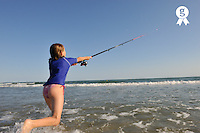 Girl fishing with reel rod from beach (Licence this image exclusively with Getty: http://www.gettyimages.com/detail/92866133 )