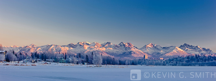 Mid winter sunset casts a pink glow on the Chugach Mountains behind Anchorage, shot from the Tony Knowles Coastal Trail along Westchester Lagoon, sunset, winter, Anchorage, Southcentral Alaska, USA.