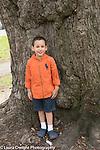 3 year old boy outside portrait standing near large tree, full length