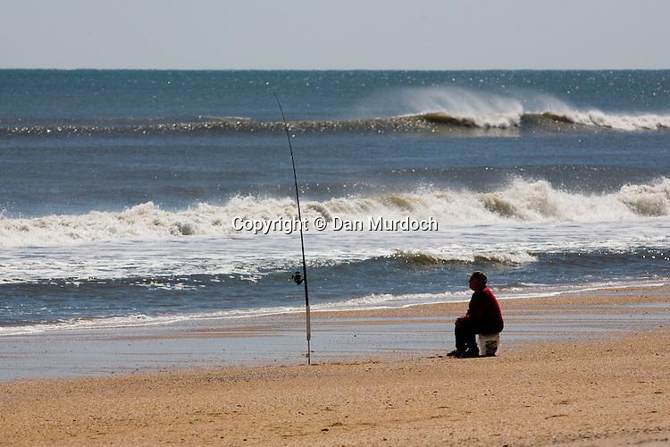 A patient fisherman surfcasting