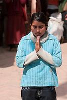 Bodhnath, Nepal.  Worshiper Prays at a Shrine at the Base of the Bodhnath Stupa, a Tibetan Buddhist Stupa.