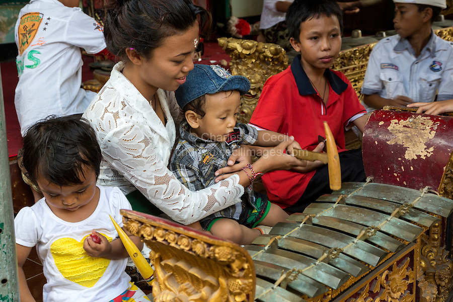 Bali, Indonesia.  Balinese Hindu Mother Showing Child how to Hit a Xylophone with its Wooden Hammer.