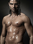 Dramatic portrait of a young man with wet bare torso standing under a shower with water running down his body Image © MaximImages, License at https://www.maximimages.com