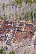 Spring snow melt and heavy rains drain down a cliff along the Kancamagus Highway in the White Mountains, New Hampshire USA.