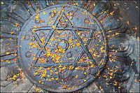 An iron hexagram covered with golden flower petals. Durbar Square, Kathmandu, Nepal.