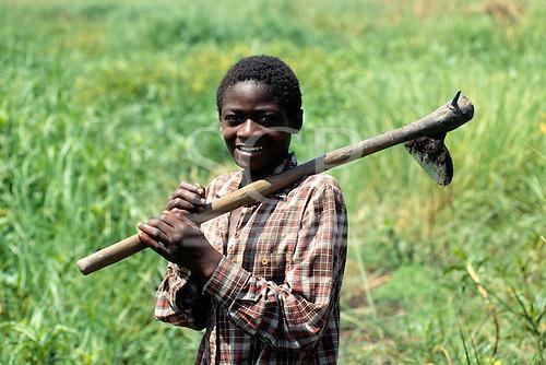 Chipundu, Zambia. Young man carrying an adze to the fields.