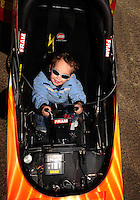 Feb. 22, 2010; Chandler, AZ, USA; Jason Beckman the son of NHRA funny car driver Jack Beckman (not pictured) sits in the cockpit of the top fuel dragster driven by Cory McClenathan (not pictured) following the Arizona Nationals at Firebird International Raceway. The race is being run Monday after weather and darkness led to the cancellation of Sunday race action. Mandatory Credit: Mark J. Rebilas-
