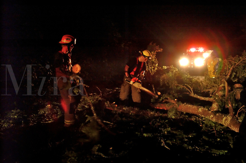 Volunteer firefighters use a chainsaw to remove a tree down across a road at night in Occidental California