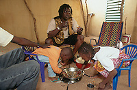 Mali. Bamako. The musician Habib Koite eats at home with a friend and two of his children. © 1997 Didier Ruef