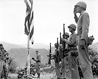 """Lt. Col. John Hopkins, commanding officer of the First Battalion, Fifth Marine Regiment, leads in singing the """"Star Spangled Banner"""" during Memorial Services held in the field during the Korean campaign.  June 21, 1951. Cpl. Valle. (Marine Corps)<br /> NARA FILE #:  127-N-A9345<br /> WAR & CONFLICT BOOK #:  1401"""
