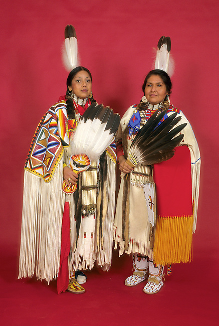 Native American family of two sisters of adult age dressed in  traditional regalia covered in beadwork. Both carry eagle wing fans and wear eagle feathers in back of braids.
