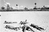 Australia. New South Wales. Sydney, Coogee Beach. Five men lie on the sandy beach. They rest and get a tan at the seaside resort. 9.3.99 © 1999 Didier Ruef