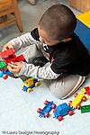 Education preschool 3-4 year olds boy building with plastic Duplo bricks blocks vertical