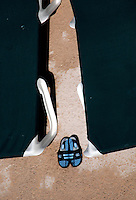 A pair of sandals sits between two chaise lounge chairs at a pool near the beach at Virginia Beach, Va.