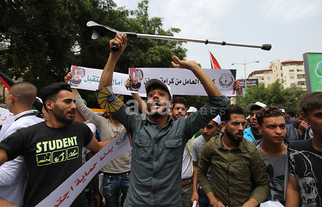 Palestinian labors chant slogans during a protest against the continued Israeli siege and the spread of unemployment to mark the International Labor Day, in front of the headquarters of the Council of Ministers, in Gaza city on May 1, 2018. Photo by Ashraf Amra