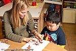 Education preschool 3-4 year olds female student teacher working with boy on nature art activity gluing fall leaves to paper horizontal