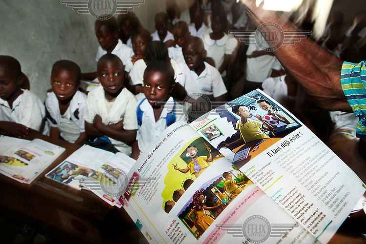 A teacher reads to his class from a new textbook at a school in Kinshasa.