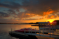 The sun rises over one of the many marinas on the Saint Lawrence River in the Thousand Islands region, with the Thousand Islands Bridge in the background.  The Thousand Islands Bridge carries traffic between New York in the USA and Ontario, Canada.