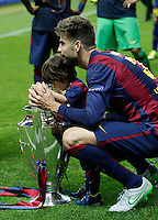 Calcio, finale di Champions League Juventus vs Barcellona all'Olympiastadion di Berlino, 6 giugno 2015.<br /> FC Barcelona's Gerard Pique' celebrates with his child at the end of the Champions League football final between Juventus Turin and FC Barcelona, at Berlin's Olympiastadion, 6 June 2015. Barcelona won 3-1.<br /> UPDATE IMAGES PRESS/Isabella Bonotto