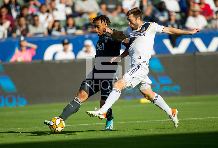 CARSON, CA - SEPTEMBER 29: Dave Romney #4 of the Los Angeles Galaxy defends against Theo Bair #50 of the Vancouver Whitecaps moves with the ball during a game between Vancouver Whitecaps and Los Angeles Galaxy at Dignity Health Sports Park on September 29, 2019 in Carson, California.