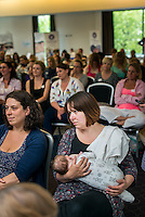 A mother  listening to a speaker while breastfeeding her baby in the auditorium at a conference.<br /> <br /> 13/06/2015