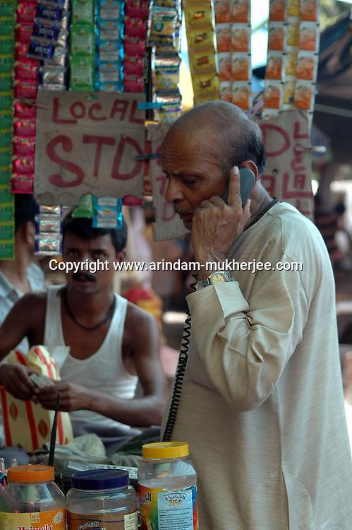 An Indian old man calling from a STD/ISD  booth at a Ciggeret shop in Kolkata, West Bengal,  India  7/18/2007.  Arindam Mukherjee/Landov
