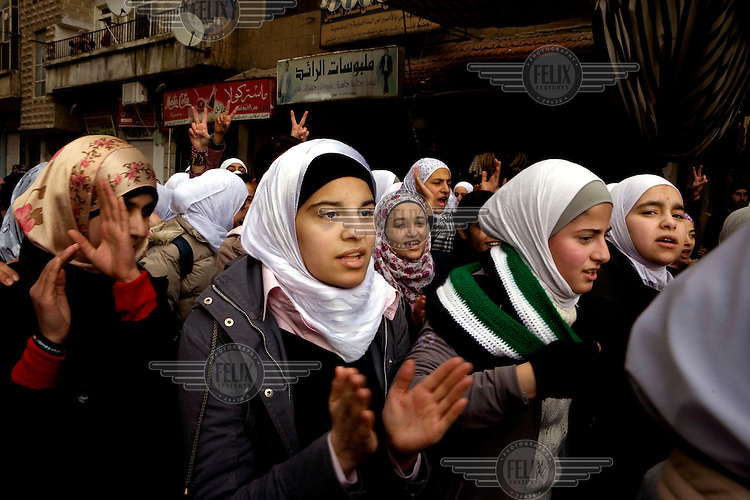 """Schoolgirls demonstrate against the Syrian regeime in the centre of Zabadani, the only town in Syria officially held by the rebels. The hill town, which is surrounded by government forces, lives in constant fear of attack. The girls shout """"We support the Free Syrian Army"""", """"Assad, go to hell"""" and """"The people want the end of the regieme"""". Protests against the ruling Baathist regime of Bashar al-Assad erupted in March 2011. Although they were initially peaceful,  they were violently repressed by the Syrian army and police. In response to being ordered to shoot unarmed civilians, large numbers of men deserted the army and formed the Free Syrian Army. The protest movement has now turned into an armed uprising with clashes between the regular army and the Free Syrian Army taking place in early 2012.."""