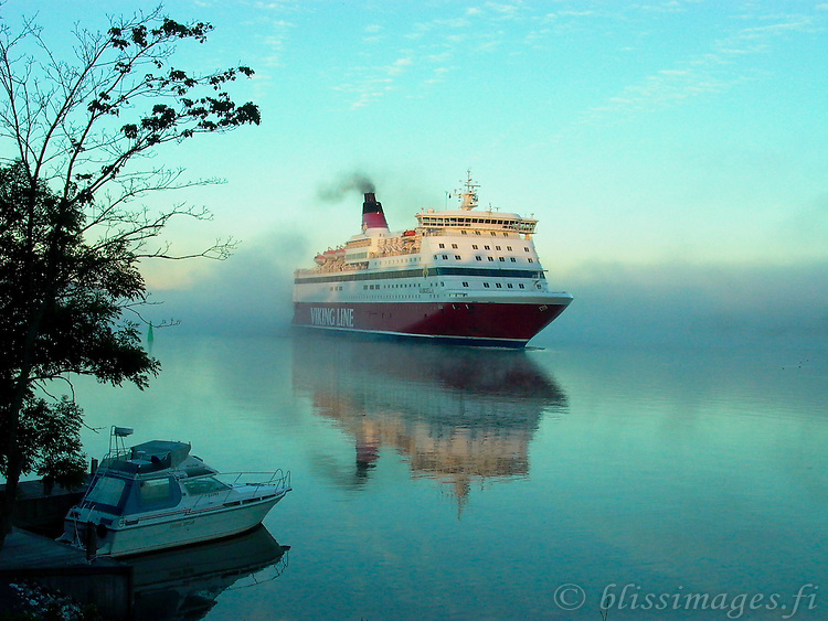 Viking Gabriella ghosts through a misty channel at sunrise.