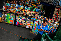 A Salvadoran bookseller works in front of piles of used books stacked on the street in a secondhand bookshop in San Salvador, El Salvador, 11 April 2018. Large collections of worn-out books, mostly textbooks and educational paperbacks, are sold regularly in secondhand bookshops in the center of the city.