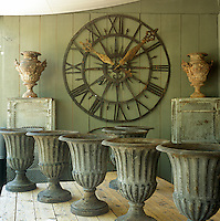 A wrought iron clock face with roman numerals and gilt hands hanging on a painted wall. In front are a collection of stone urns.