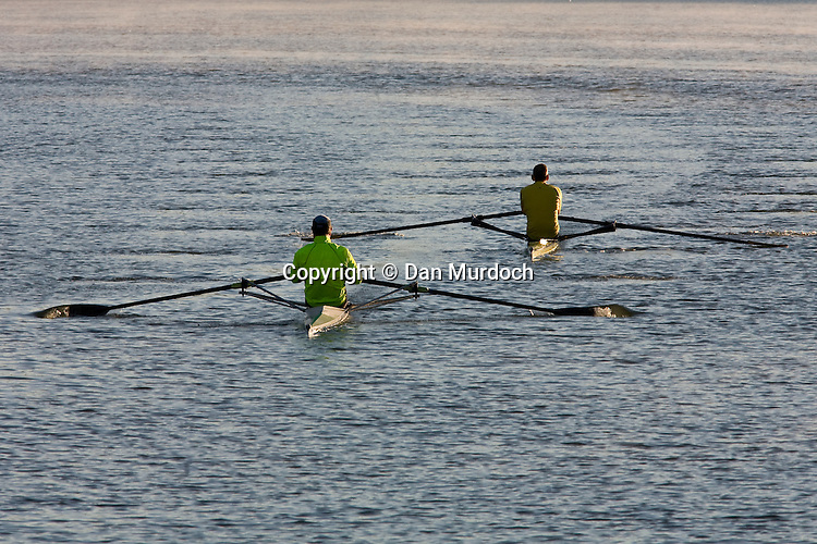 two single sculls rowing on a river